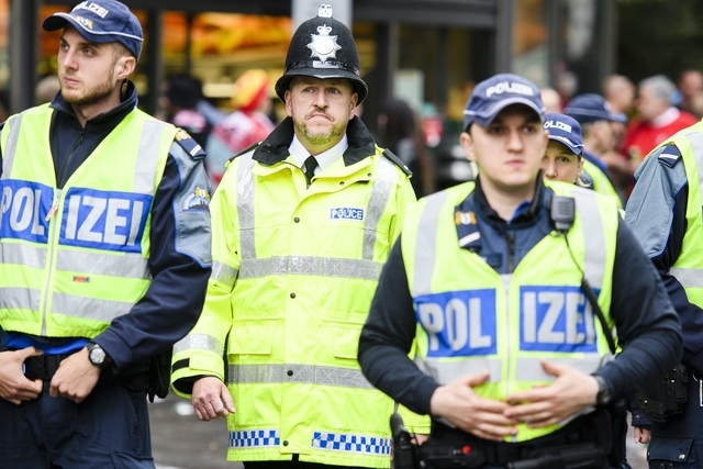 """A british police officer, Bobby, stands between two swiss police officers on the """"Barfuesser"""" place in Basel ahead of the UEFA Europa League final between England's Liverpool FC and Spain's Sevilla Futbol Club at the St. Jakob-Park stadium in Basel, Switzerland, on Wednesday, May 18, 2016. (KEYSTONE/Manuel Lopez)"""