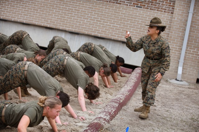 PARRIS ISLAND, SC - FEBRUARY 27: Drill Instructor SSgt. Jennifer Garza of Kerrville, Texas disciplines her Marine recruits with some unscheduled physical training in the sand pit outside their barracks during boot camp February 27, 2013 at MCRD Parris Island, South Carolina. Female enlisted Marines have gone through recruit training at the base since 1949. About 11 percent of female recruits who arrive at the boot camp fail to complete the training, which can be physically and mentally demanding. On January 24, 2013 Secretary of Defense Leon Panetta rescinded an order, which had been in place since 1994, that restricted women from being attached to ground combat units. About six percent of enlisted Marines are female. (Photo by Scott Olson/Getty Images)