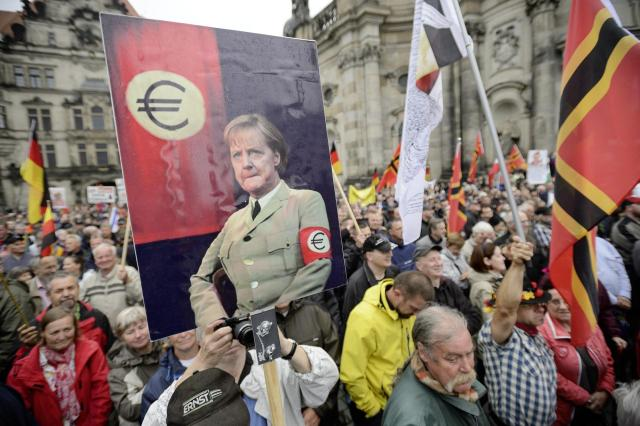 huGO-BildID: 45404445 Supporters of the German right-wing movement PEGIDA (Patriotic Europeans Against the Islamisation of the Occident) hold up a poster showing German Chancellor Angela Merkel in a uniform with an Euro-logo-armband as they attend a PEGIDA rally on June 1, 2015 in Dresden, eastern Germany. AFP PHOTO / JENS SCHLUETER